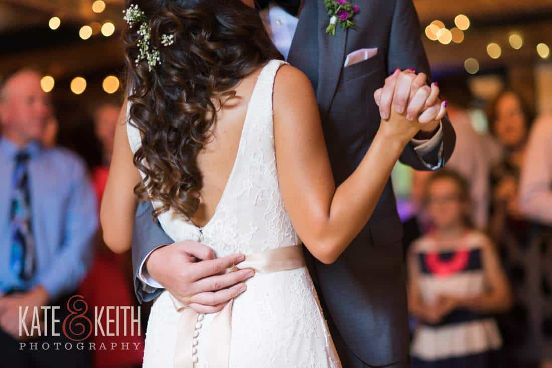 Bride and groom first dance in barn lights