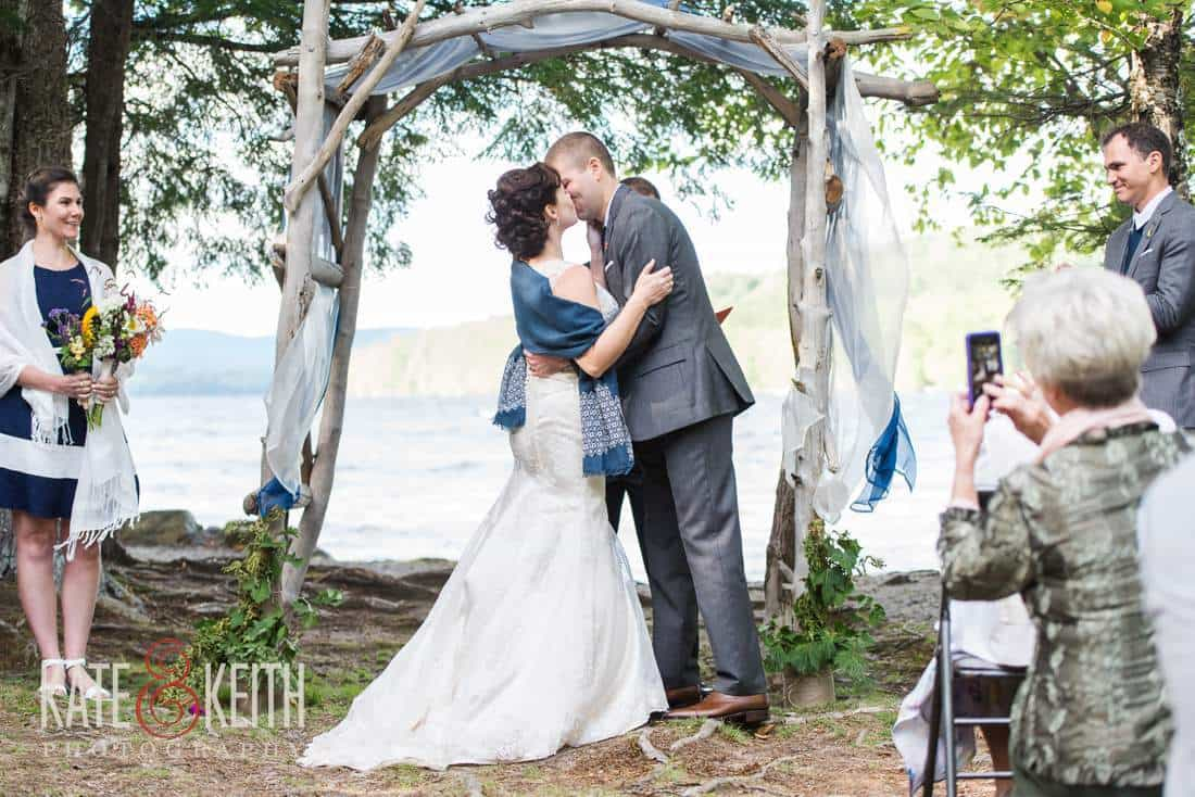 breezy lakeside wedding ceremony first kiss
