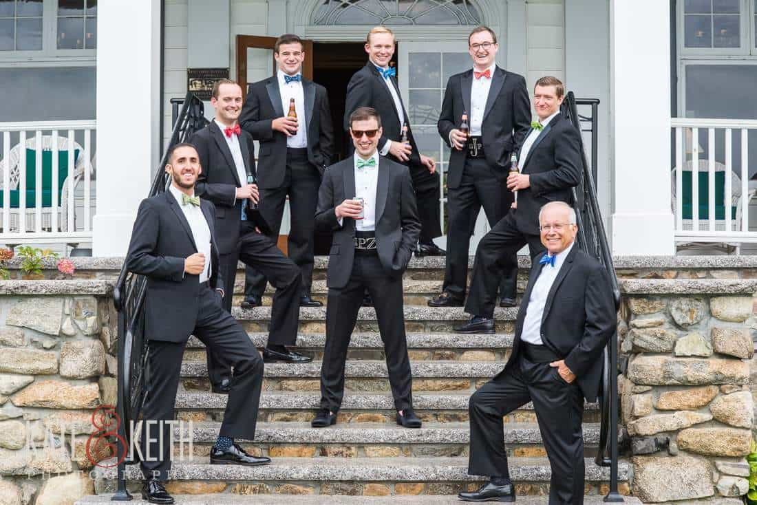Groomsmen holding beer on stairs at Colony Hotel Maine