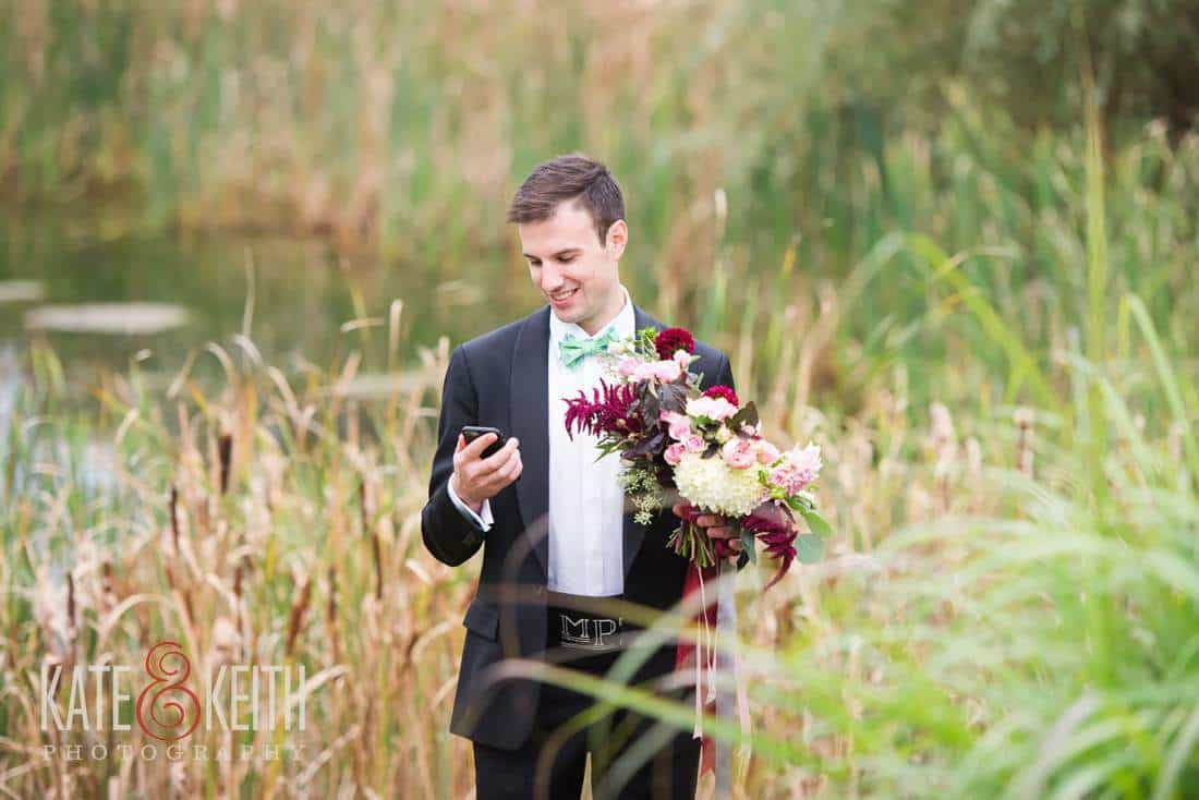 Groom checking phone, holding flowers in field