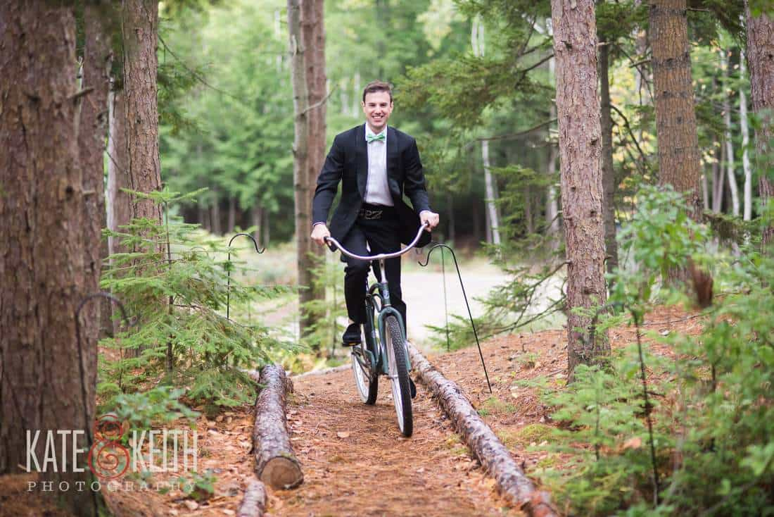 Formal groom on a bicycle in woods on trail