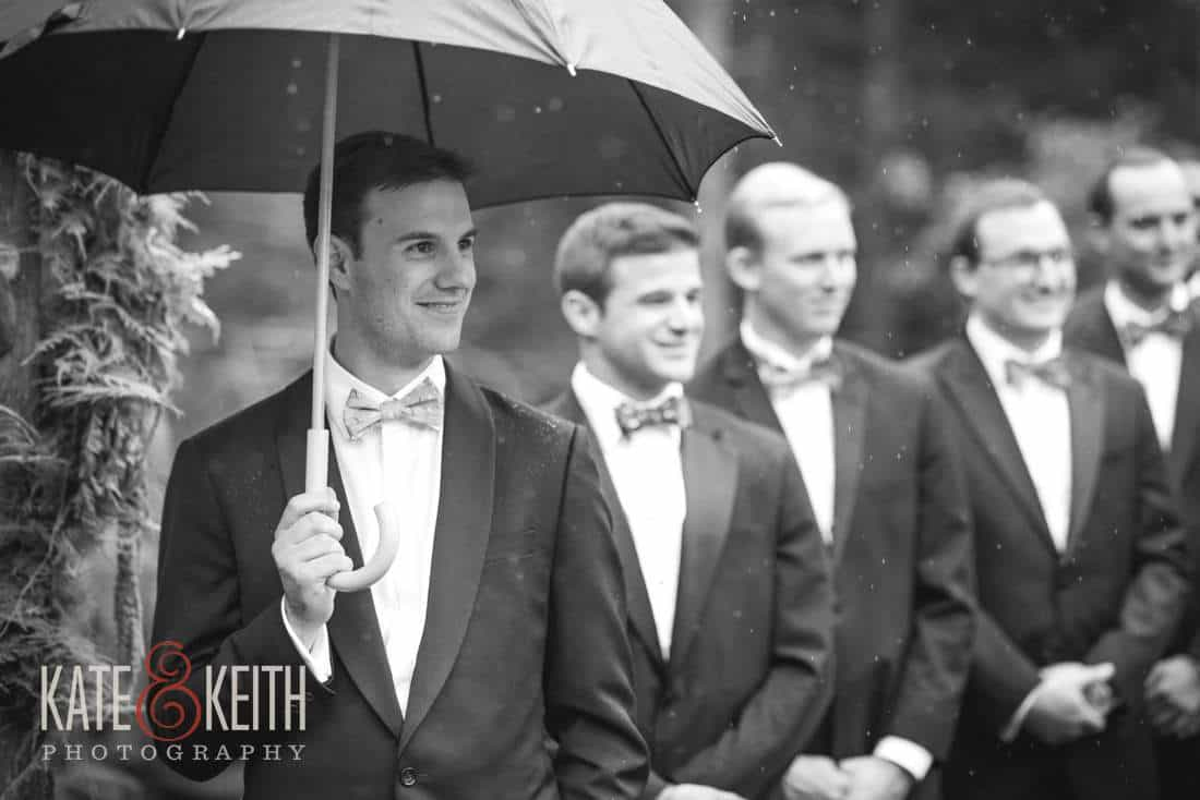 Groom with umbrella rainy wedding