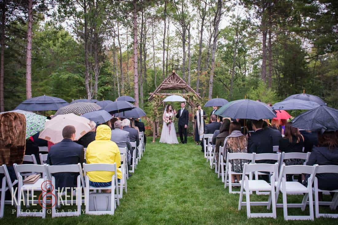 Bride and groom under umbrella rainy wedding