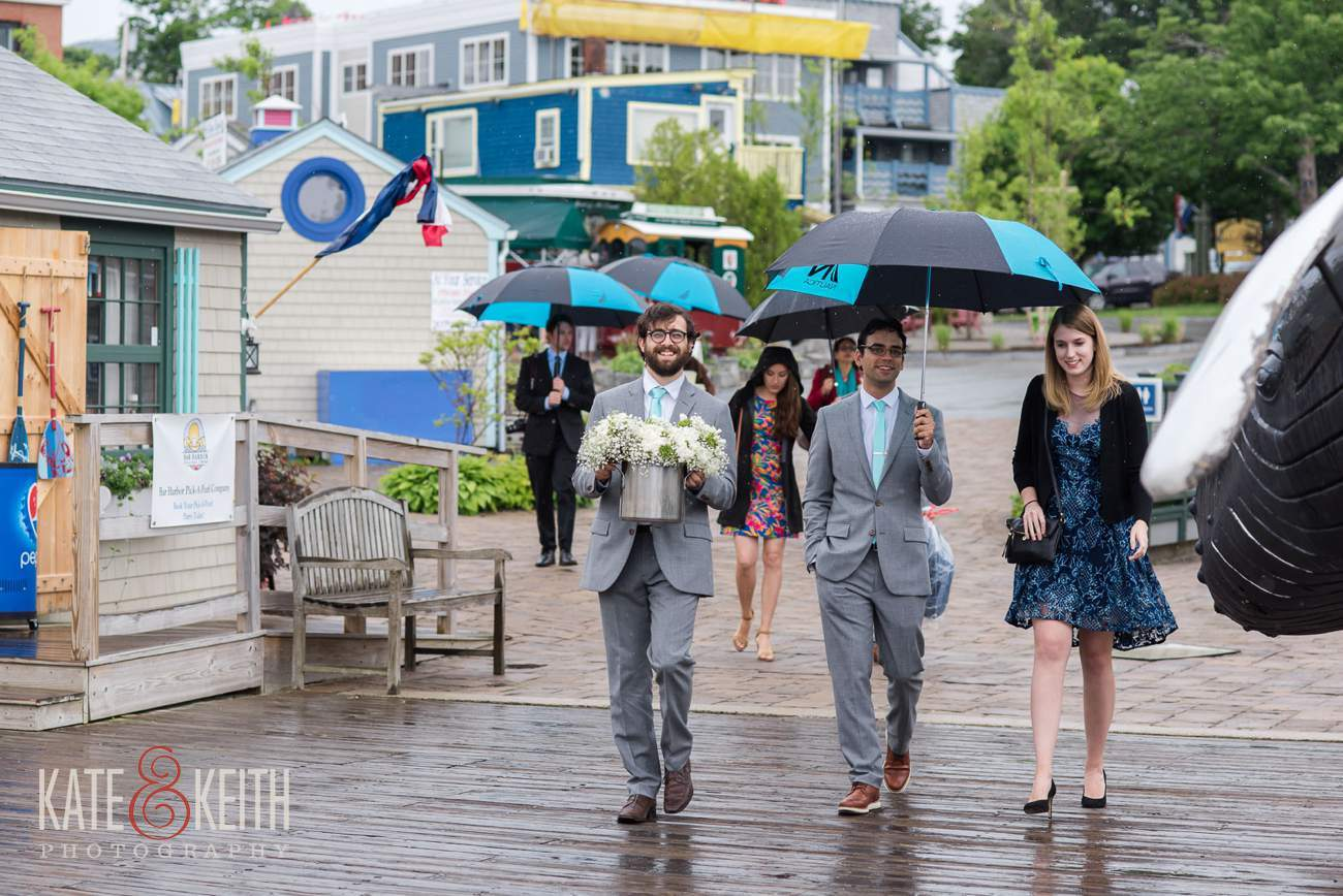 Wedding party in rain with umbrellas