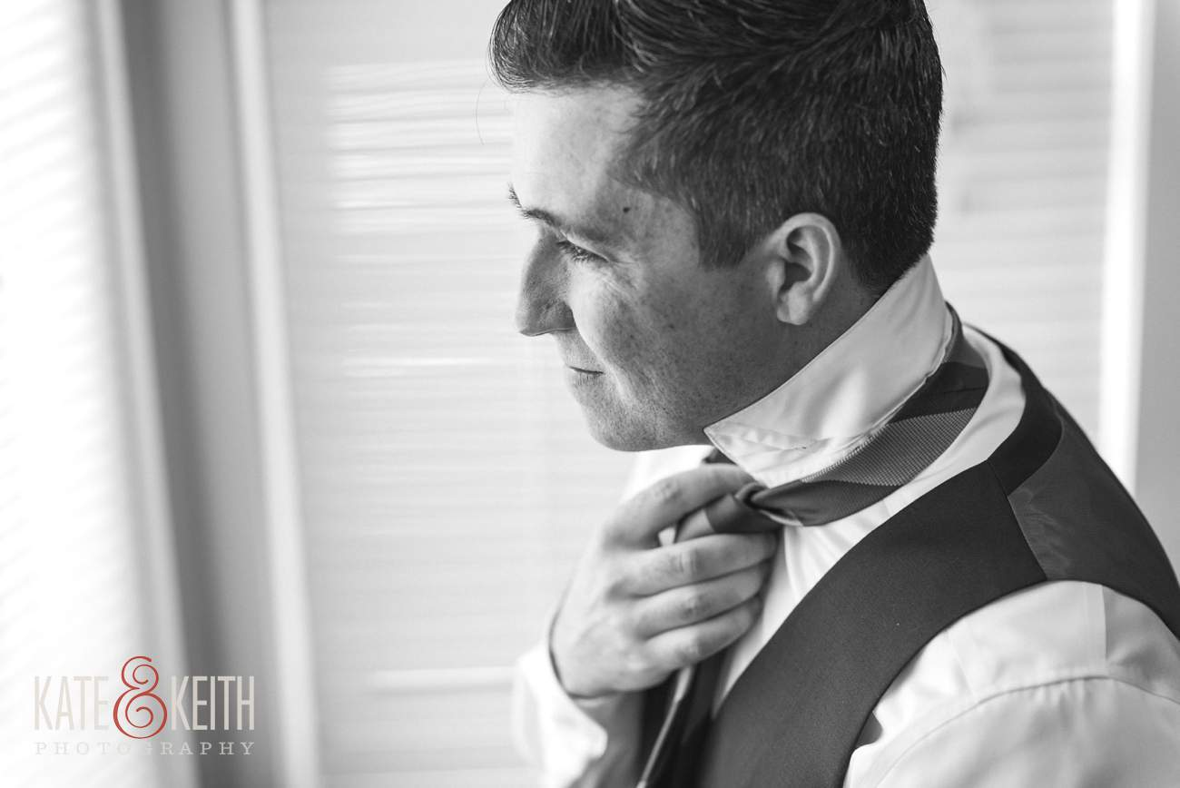 Groom adjusts tie typical wedding prep photo