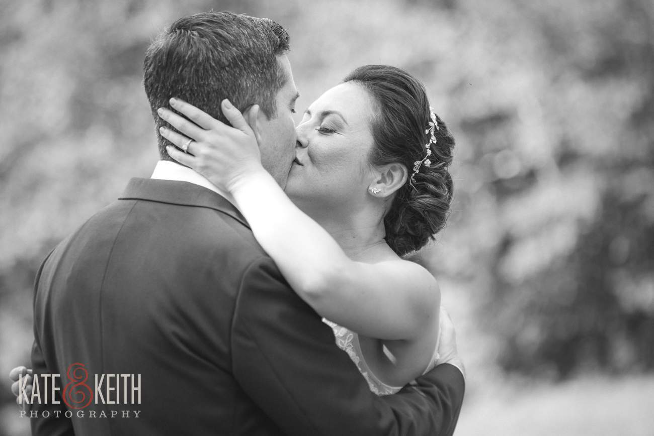 Black and white wedding photo, bride and groom kissing