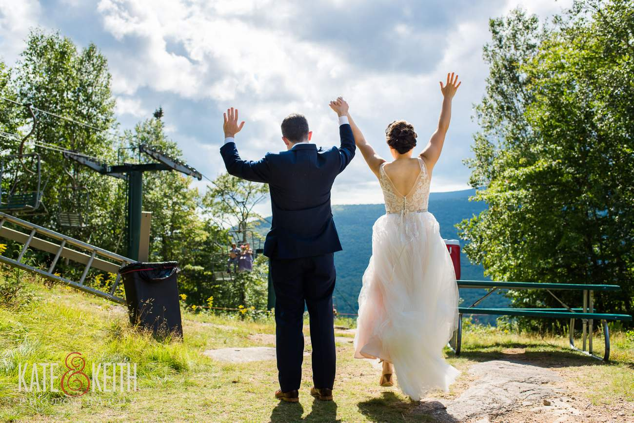 Excited bride and groom on top of mountain