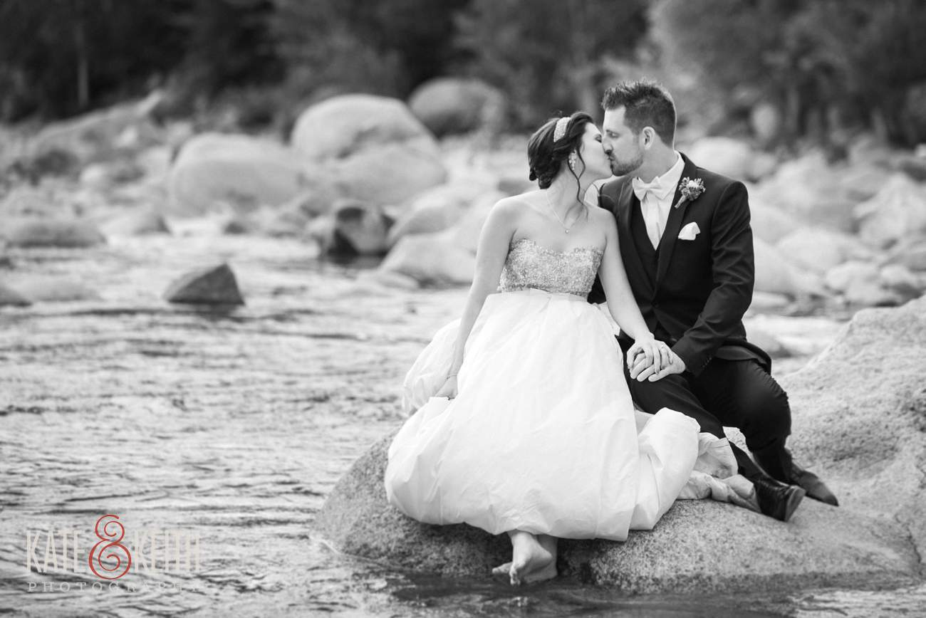 Bride and groom on rocks in river