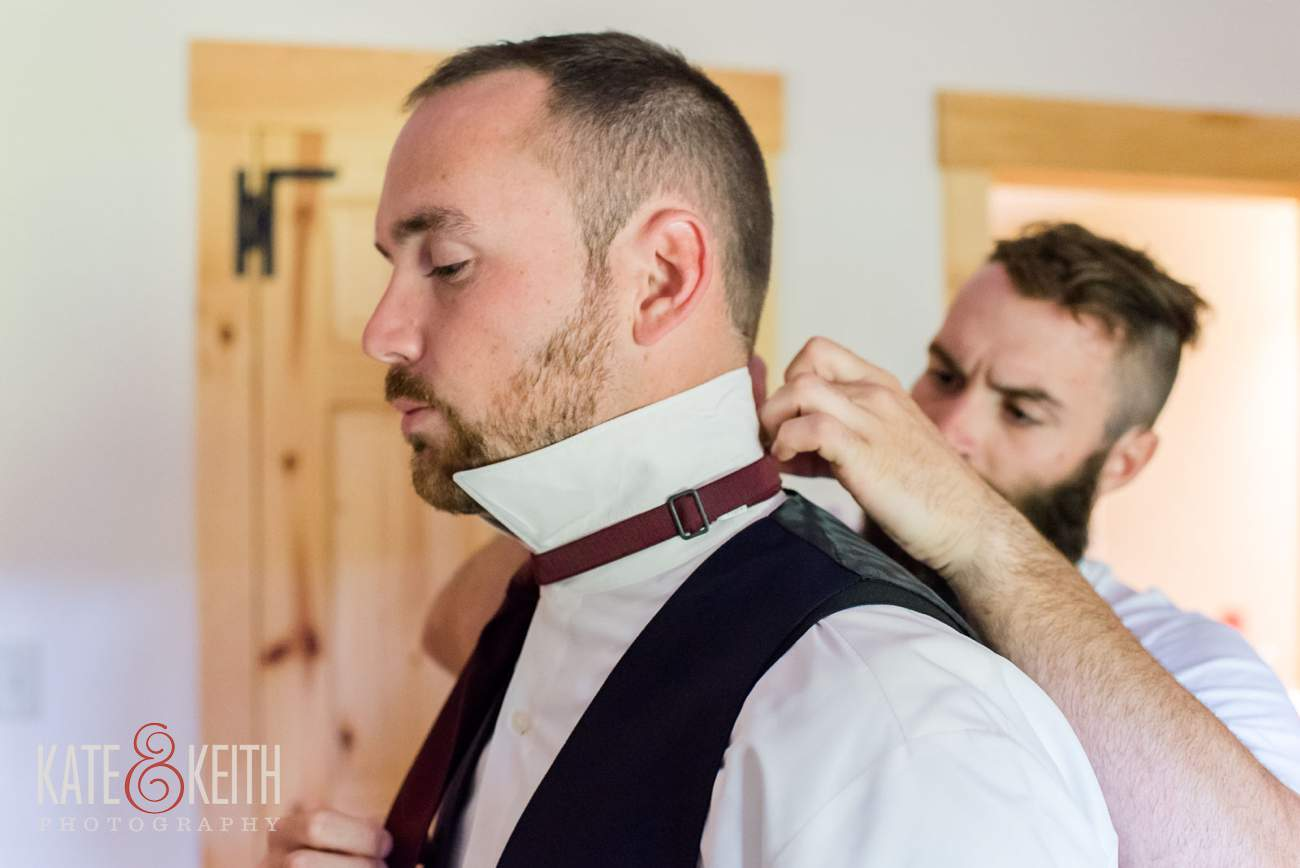 groom gets help with bowtie