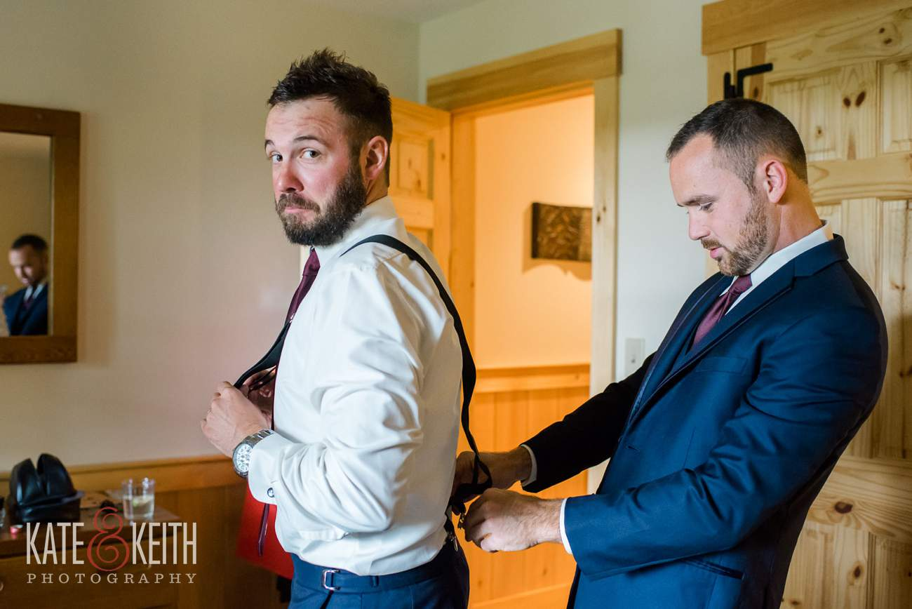 Groom helps with suspenders