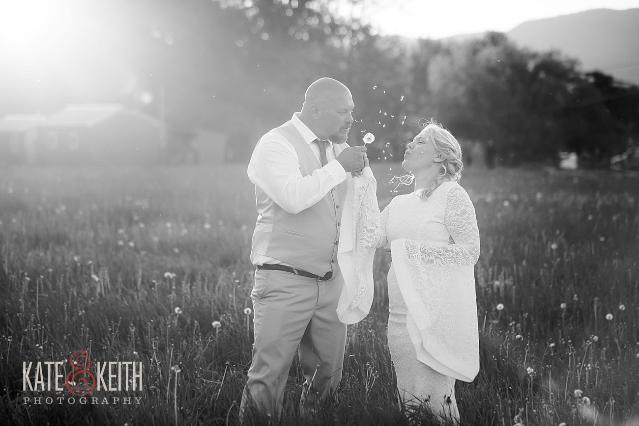 Bride and groom blowing dandelion
