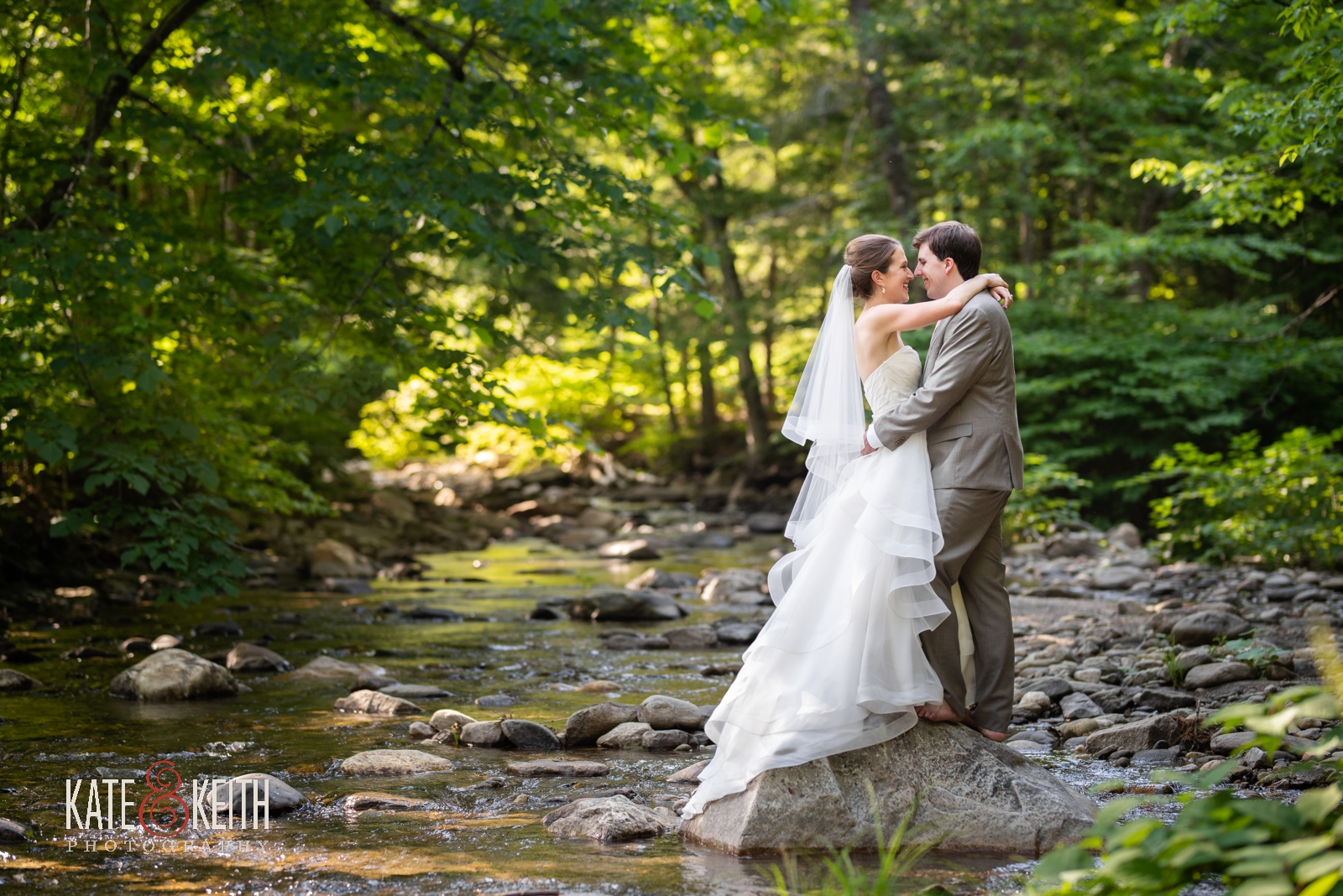wooded outside wedding photos of bride and groom in near stream in Vermont