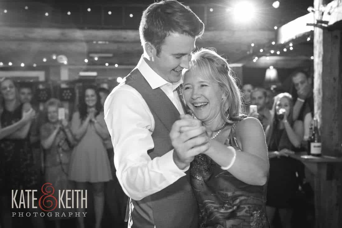 Groom and mom dance in barn
