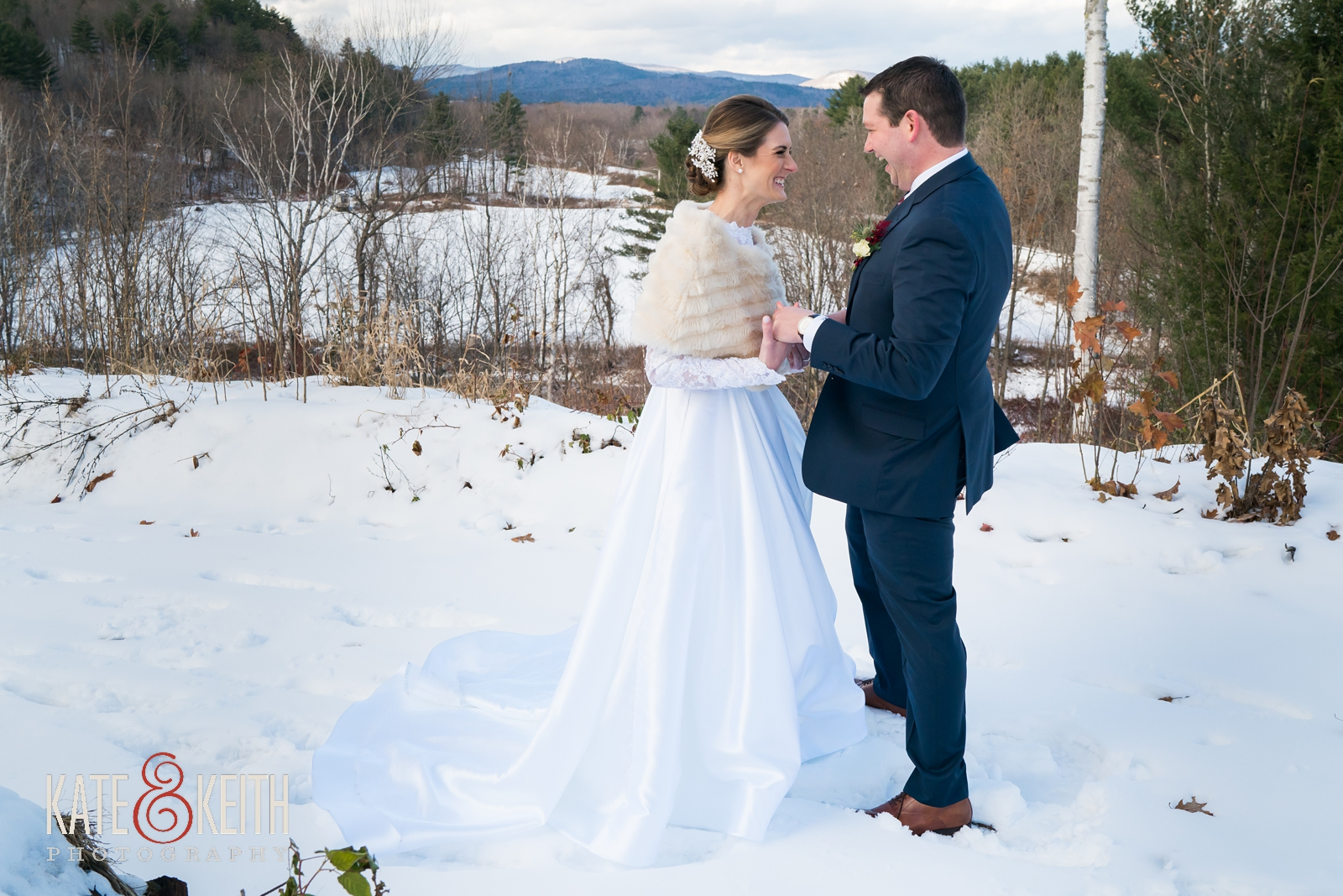 Barn on the Pemi, Your Dreams Bridal shop, Men's Warehouse, Joseph Abud, First look, wedding first look, snow, winter wedding, candid moment, fur wrap, winter wedding dress, long sleeved winter wedding dress, cold weather wedding, bride and groom first look laughing, navy suit