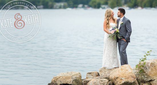 Bride and groom on rocks on shores of Lake Winnipesaukee, New Hampshire