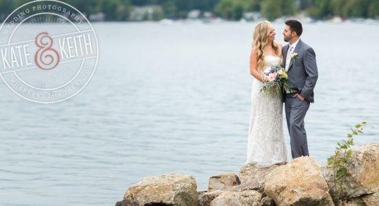 Bride and groom on rocks on shores of Lake Winnipesaukee, New Hampshire