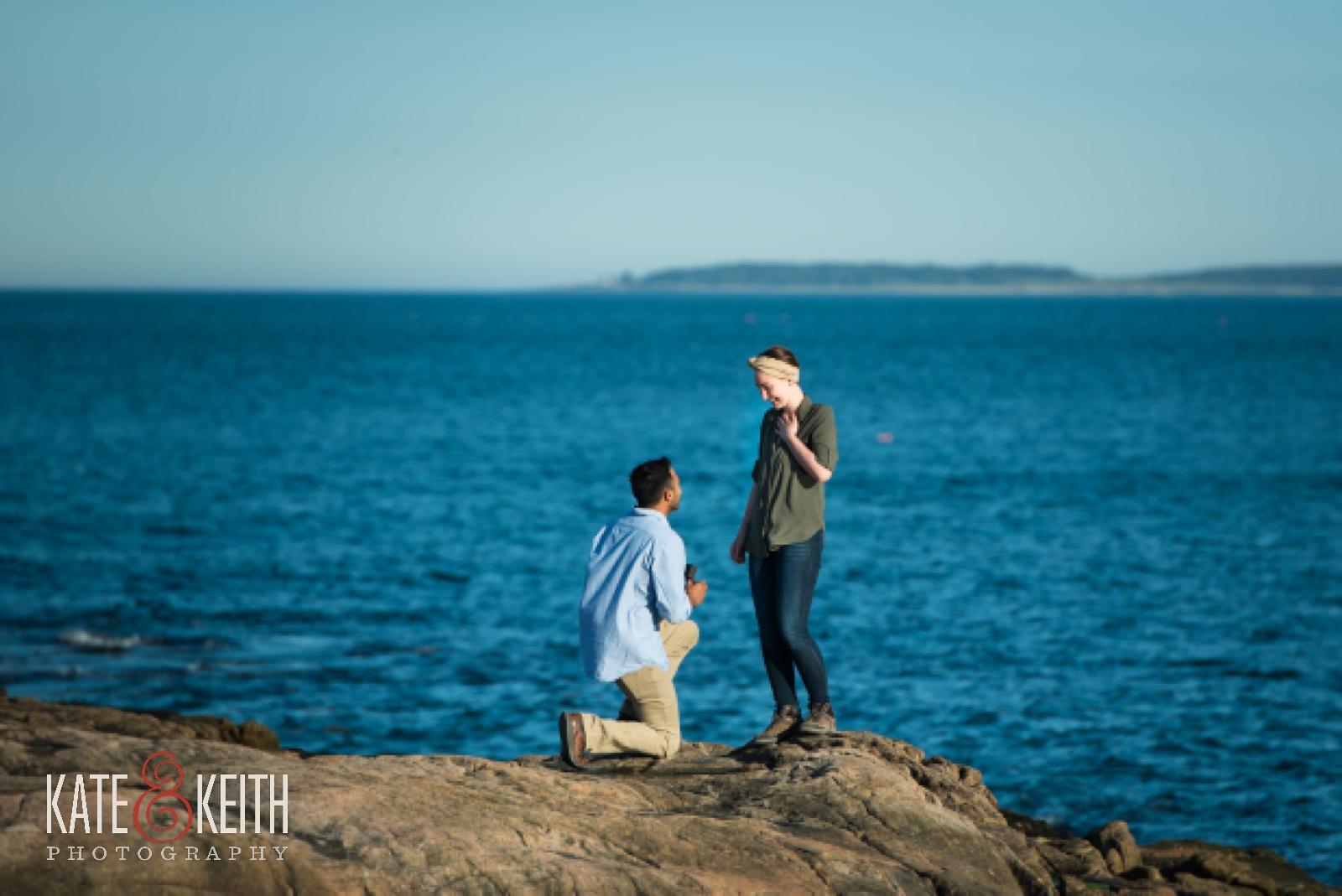 Man proposing to woman in Acadia National Park, engagement, water, ocean, sea, seaside, surprise proposal, surprise wedding proposal, rocky coast, Maine, sunset