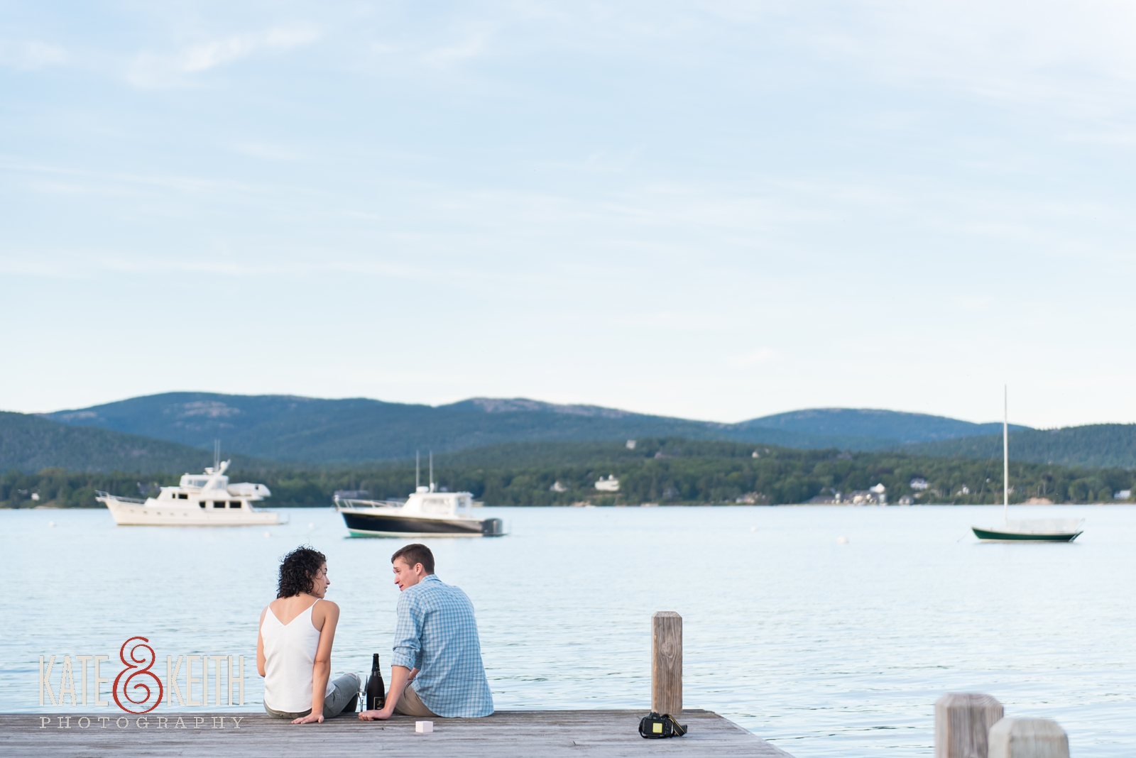 champagne celebration, celebratory toast, surprise proposal, proposal in Acadia National Park, Southwest Harbor, Mount Desert Island, seaside, sunset proposal, engagement, getting engaged in Acadia National Park, rowboat, coastal Maine, New England, sailboats, dock, waterfront engagement